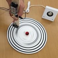 音の信号が印刷されたレコードにスピーカーが繋がった読取機を当てている様子