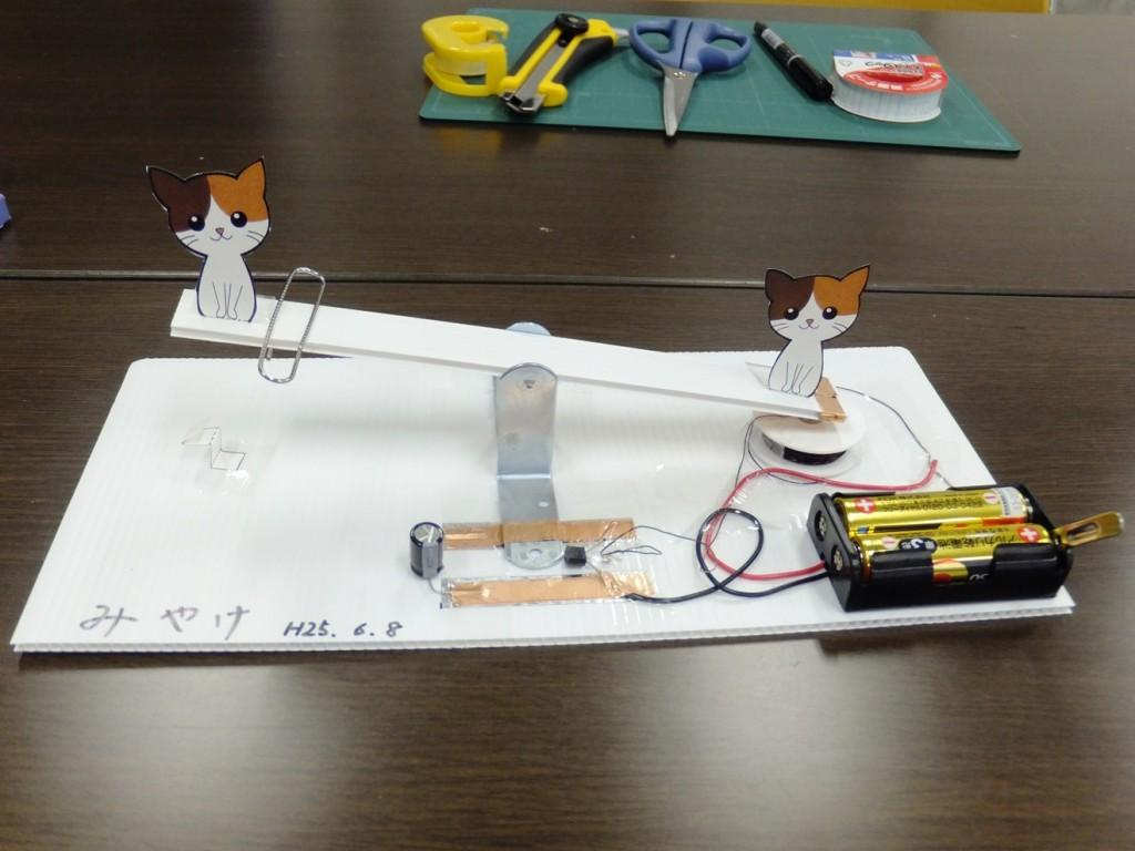 紙で作った猫を乗せたシーソー 片方のシーソーの下には磁石があり電源のON・OFFでシーソーが動きます